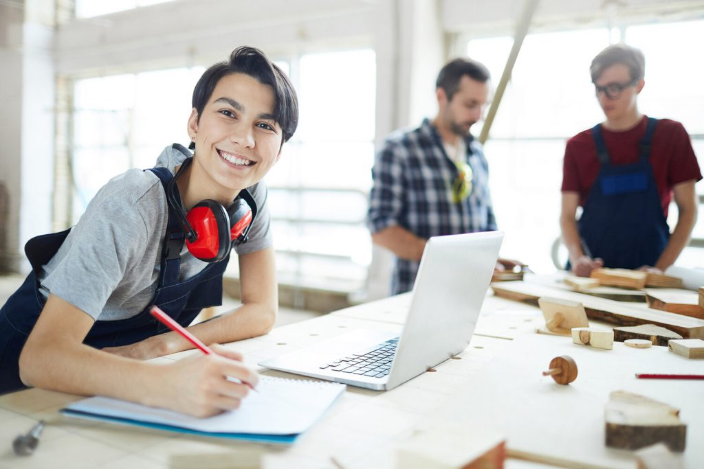 Cheerful excited young lady with ear protectors on neck leaning on table and smiling at camera while enjoying work in carpentry